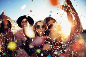 Teenager-hipster-friends-partying-by-blowing-colorful-confetti-from-hands-513550806_8660x5773.jpeg
